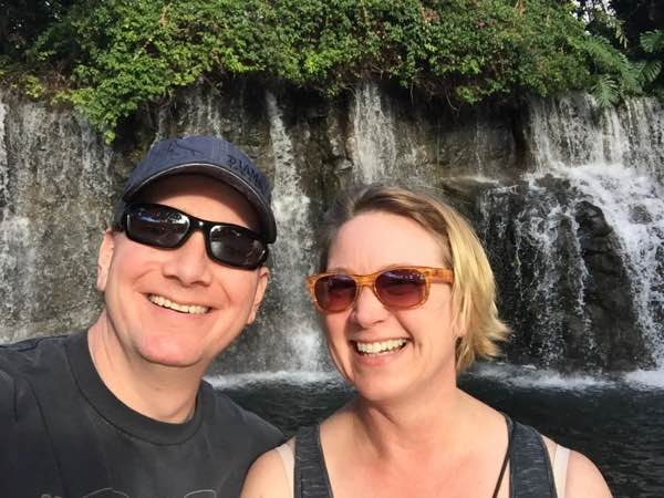 photo of Dori and Jim Settles in front of a waterfall